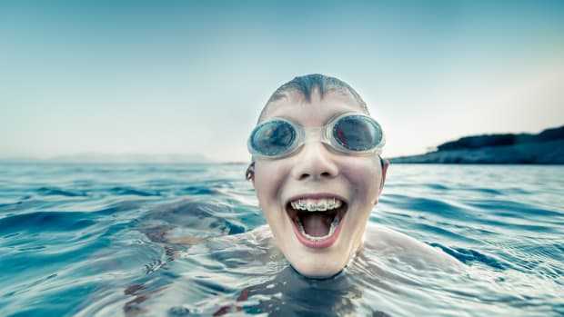 Boy with braces swimming and laughing
