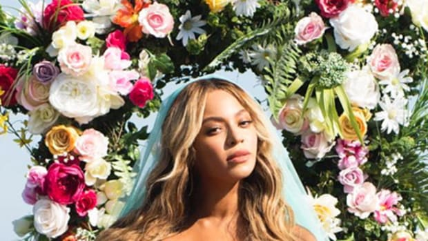 Beyonce with blue veil posing with her new twins in front of flowers