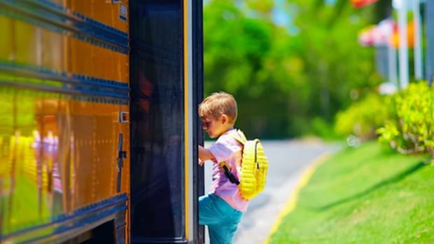 young boy kid getting on the school bus ready to go to school ** Note: Shallow depth of field