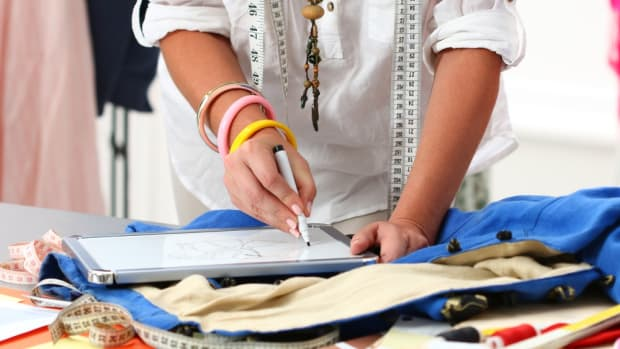 Close-up of adult female dressmaker drawing clothing design