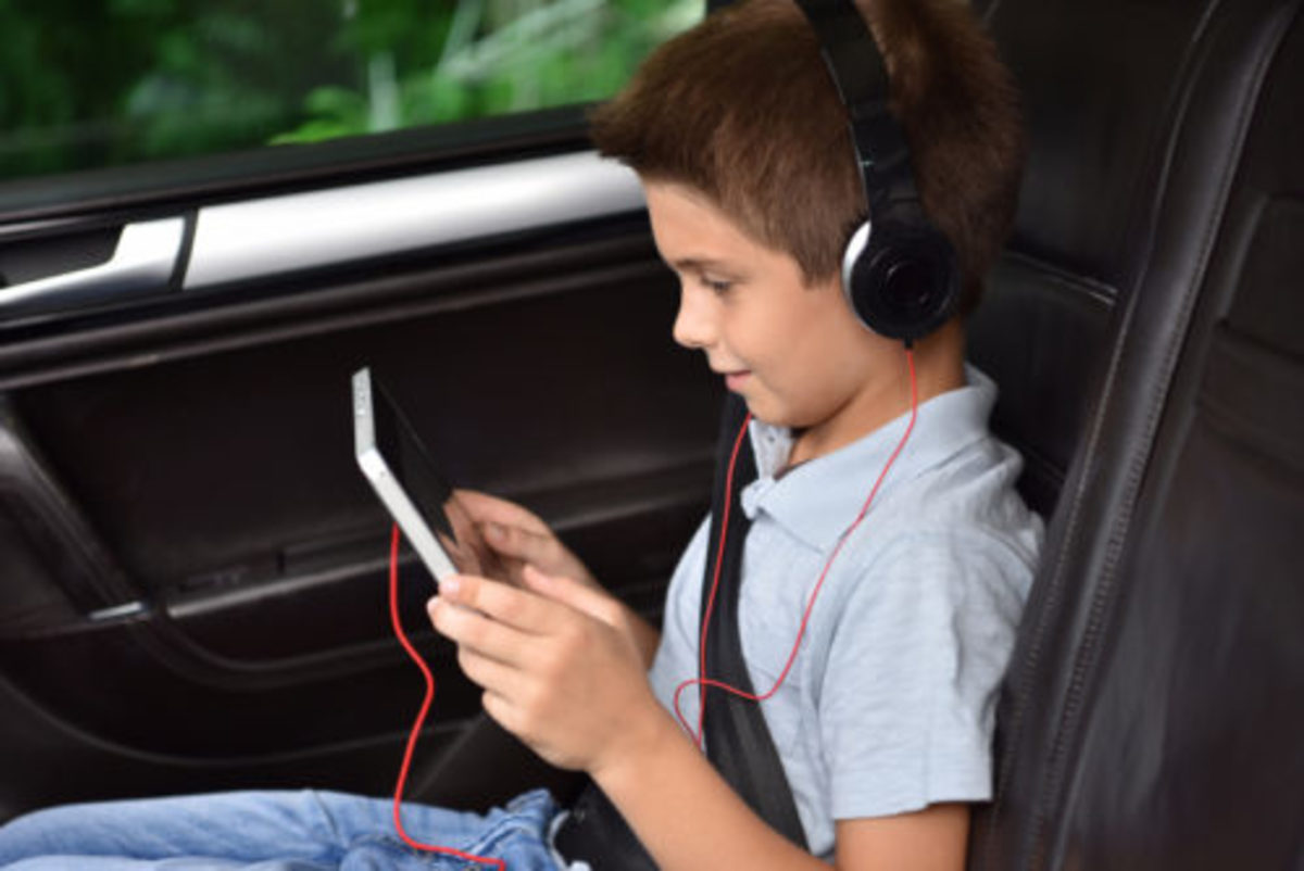 Kid watching moving on tablet inside car