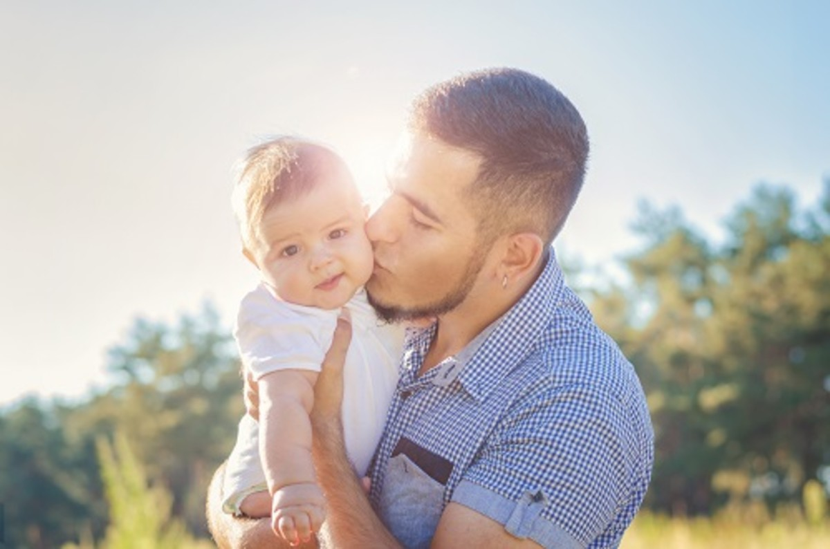 Young daddy kissing a baby. Walk autumn evening outdoors. Solar flare illuminates the baby and dad.