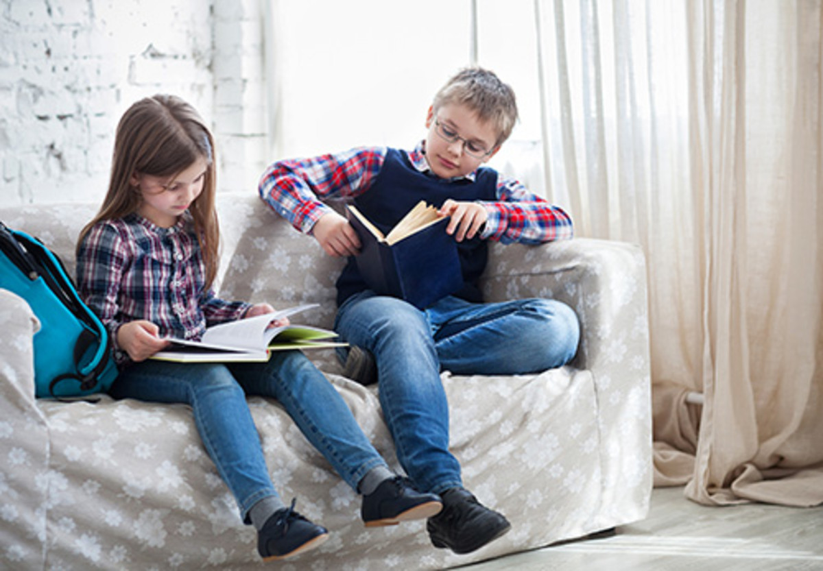 Children readind book in living room siting on the sofa