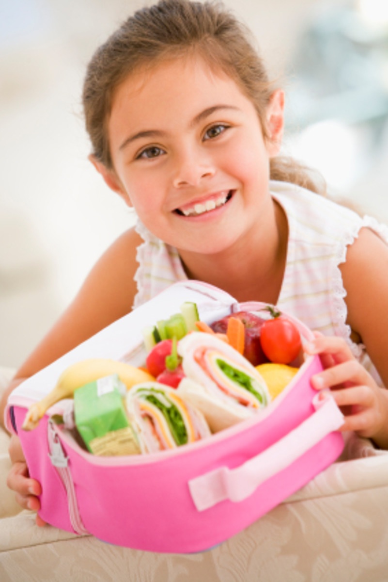 Young girl holding packed lunch in living room smiling